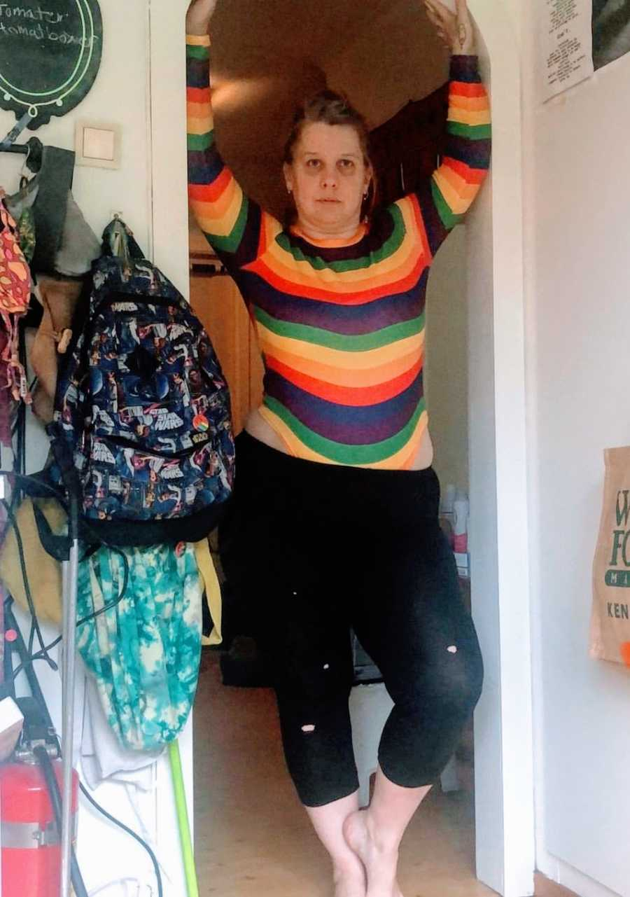 A nonbinary person wearing a rainbow striped shirt stands in a doorframe