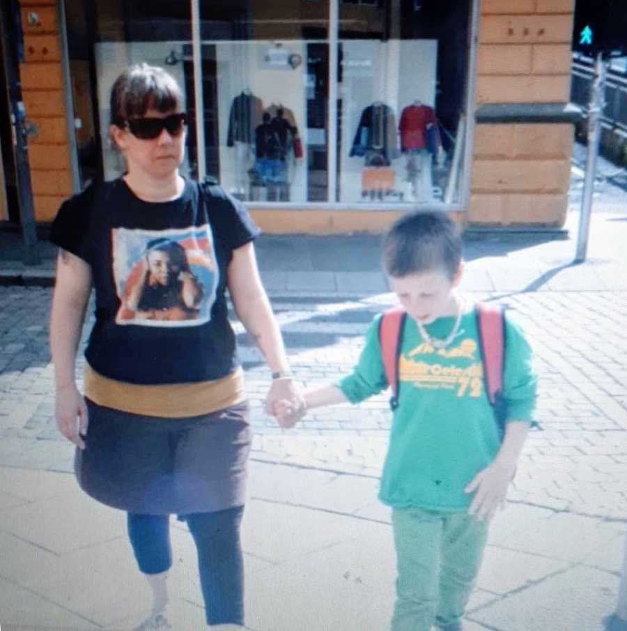A nonbinary person and their son walking while holding hands