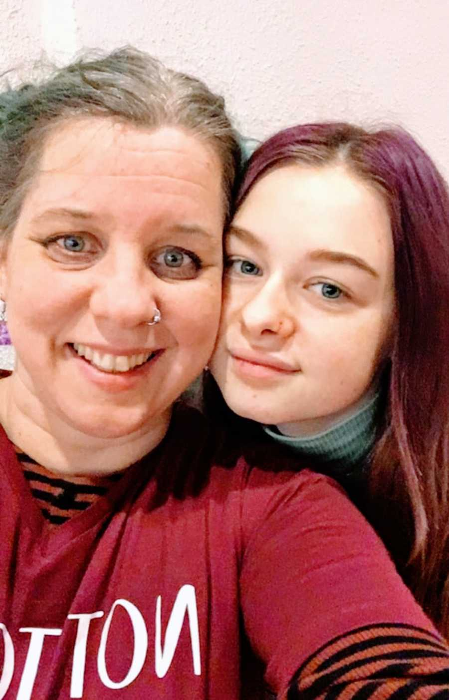 A nonbinary person and their daughter with faces pressed together for a photo