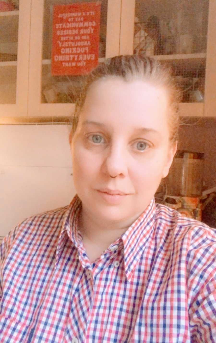 A nonbinary person wearing a red and blue checkered shirt