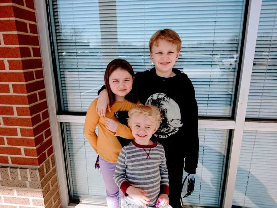 Three siblings stand together near a window