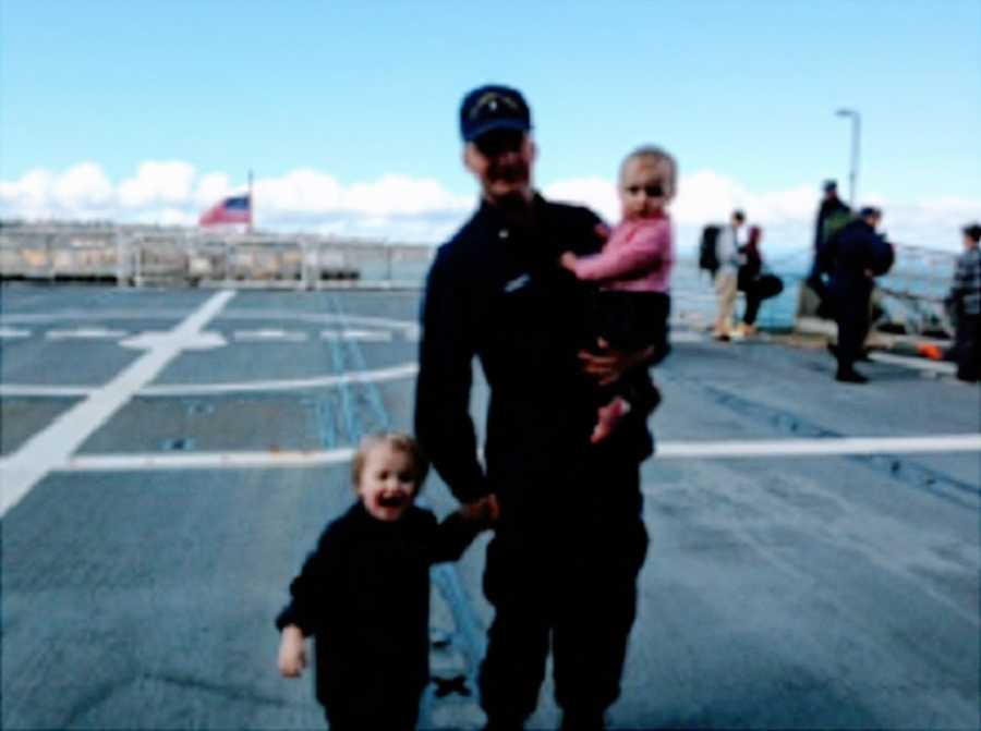 A father stands with his two children on a tarmac
