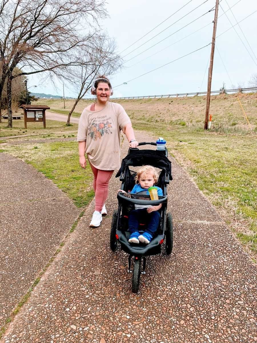 A mother takes her toddler for a walk in a stroller
