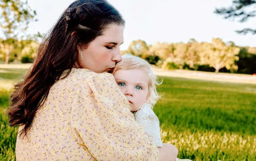 A mother hugs her baby in a field