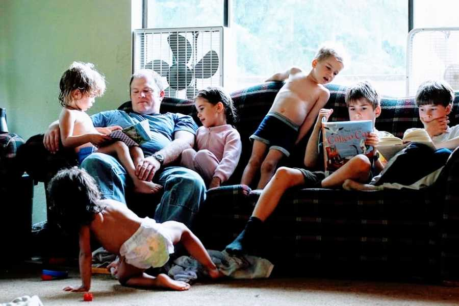 A father sits on the couch with his six children