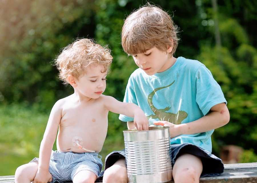 A pair of brothers play with a can outside