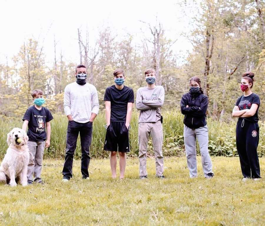 A group of siblings stand together wearing masks