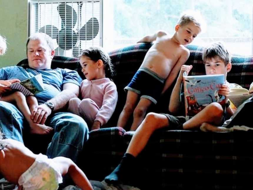 Six kids sit with their father on a couch