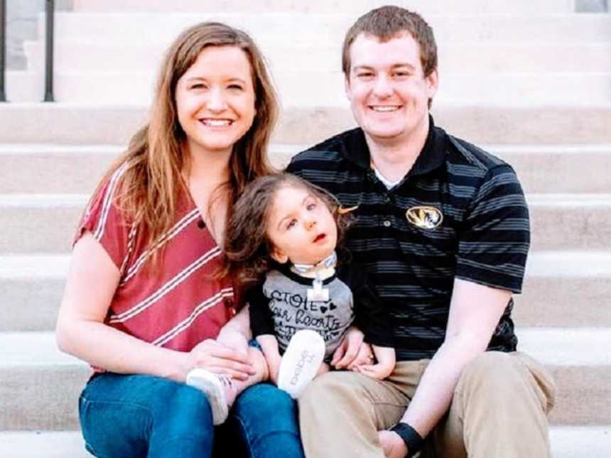 Parents sit with their adopted daughter on courthouse steps