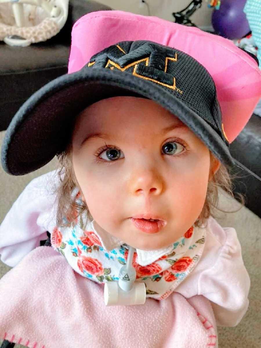 A little girl wearing a baseball cap