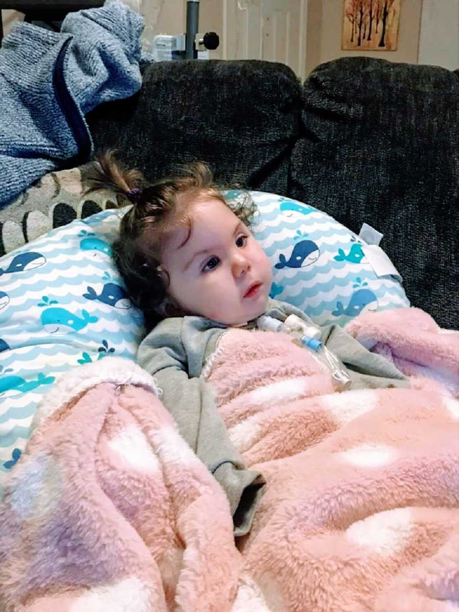A little girl lies on a pillow and looks off at something