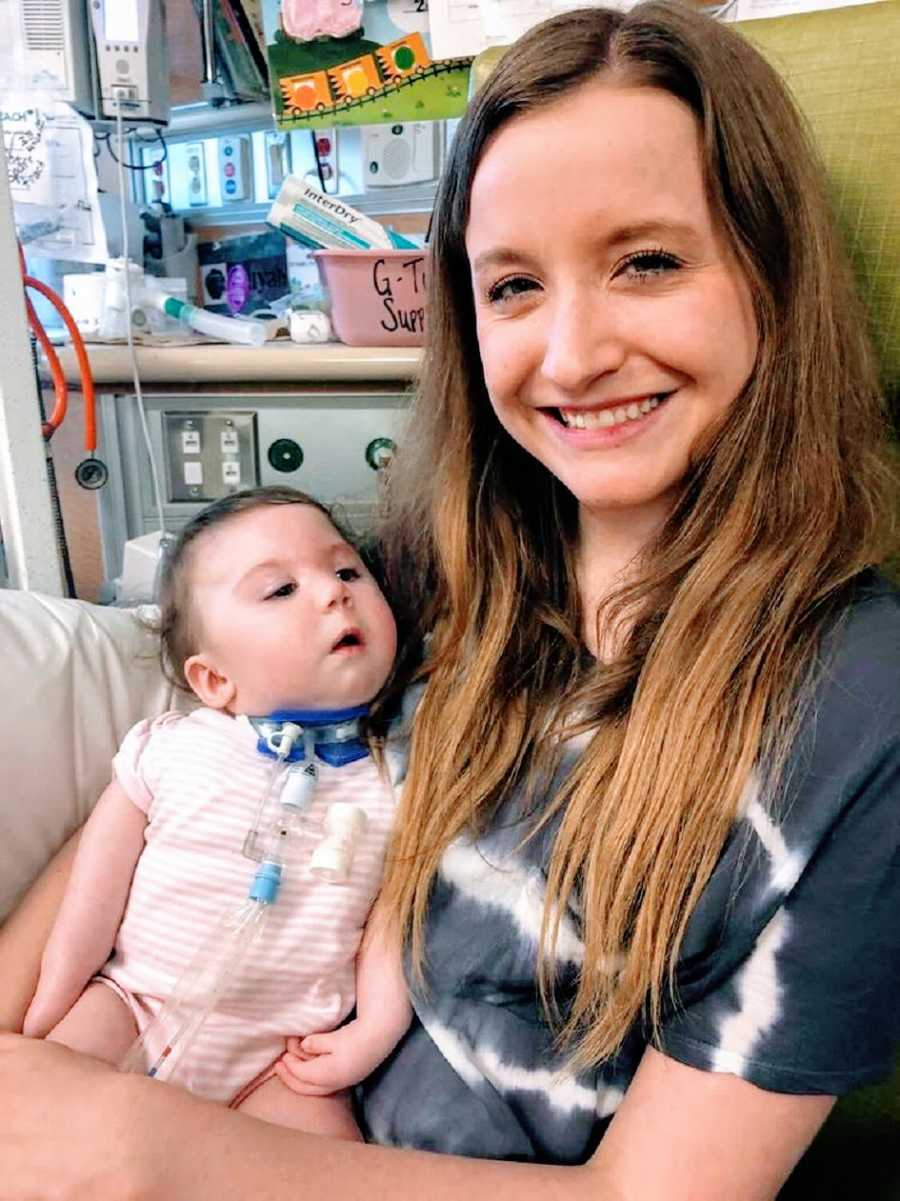 A woman sits in the hospital with a baby girl