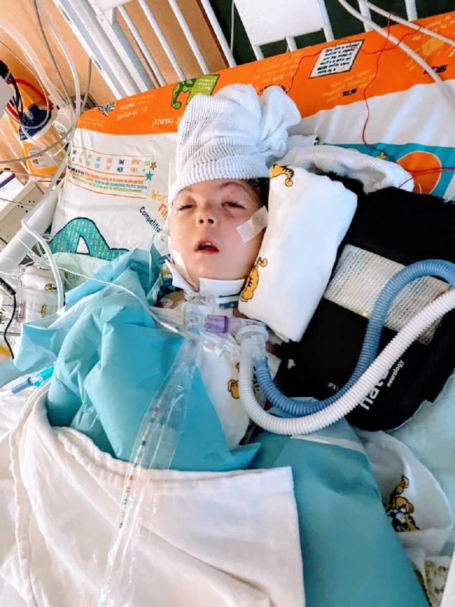 A little girl lying in a hospital bed attached to several tubes