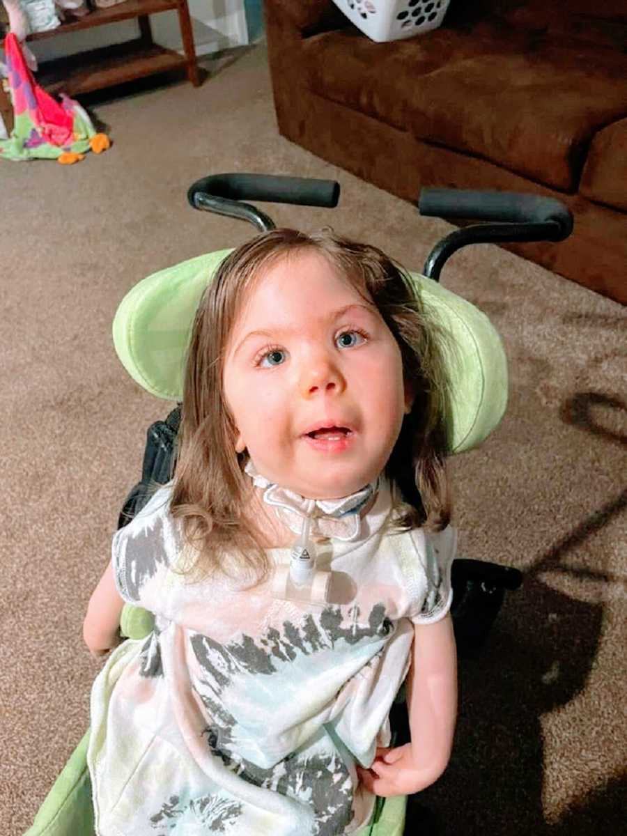 A little girl sits in a green wheelchair