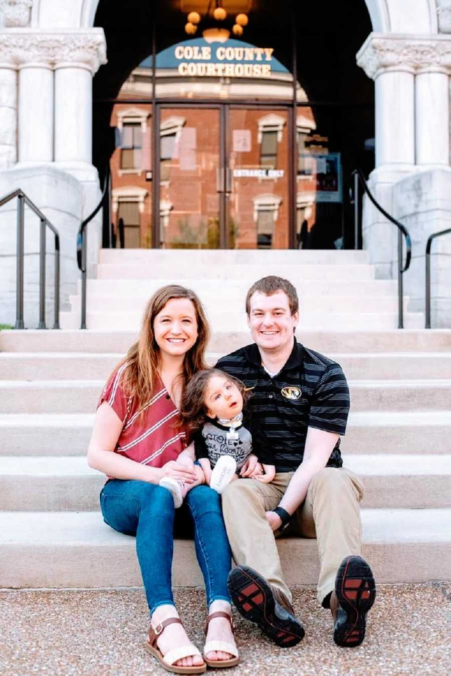 Parents sit on steps with their adopted daughter