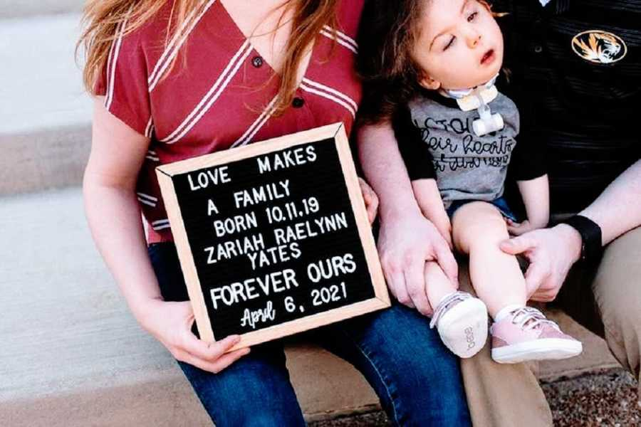 A mother sits holding a sign with her baby girl