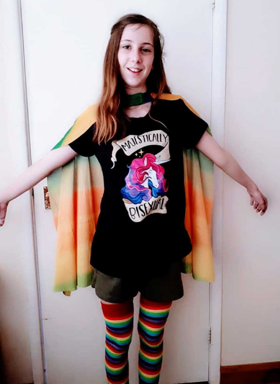 A bisexual child wearing a pride shirt and a cape