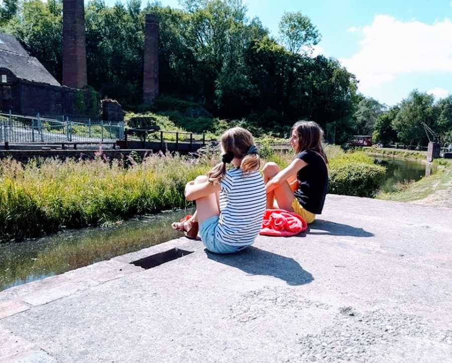Two children sit together by the water
