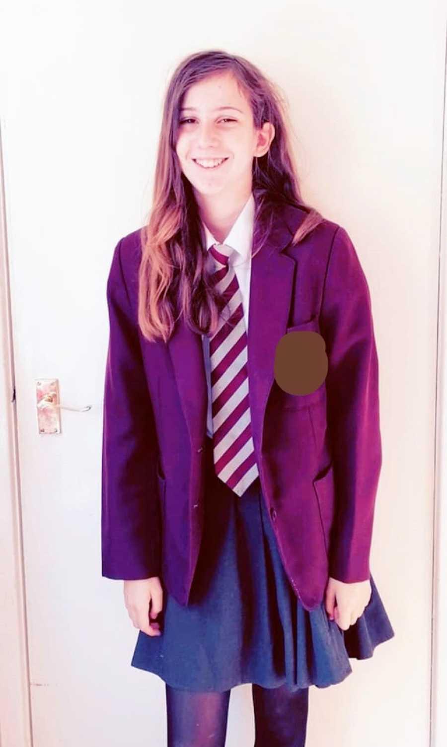 A child stands in a school uniform