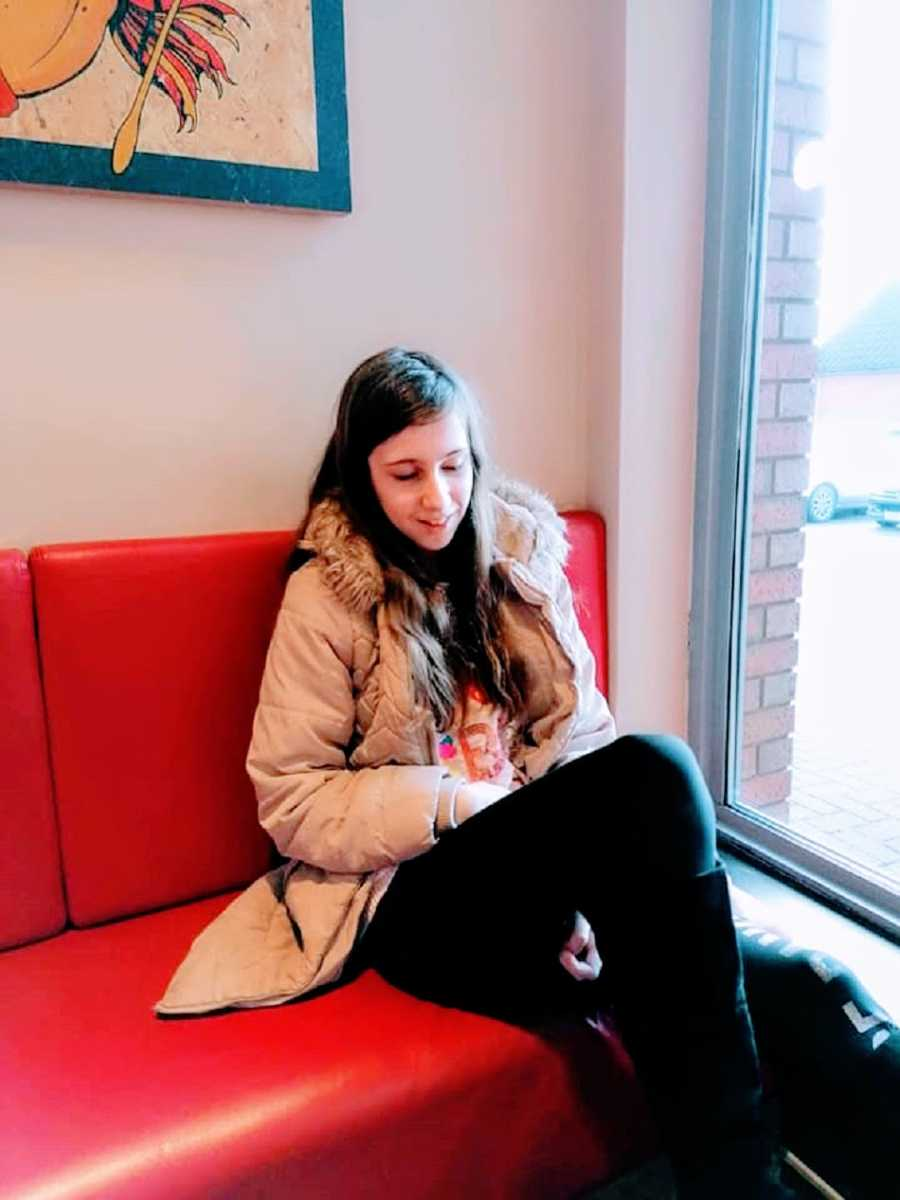 A child sits in a red seat wearing a coat