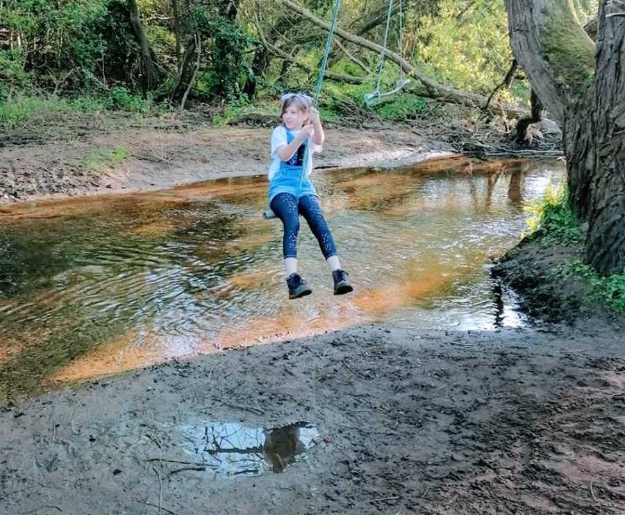 A girl with autism plays on a swing over water
