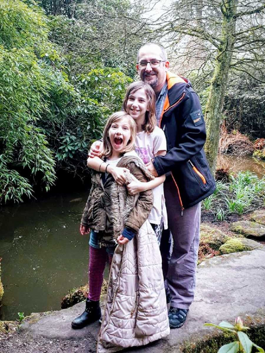 A father stands with his two children on a rock in a pond