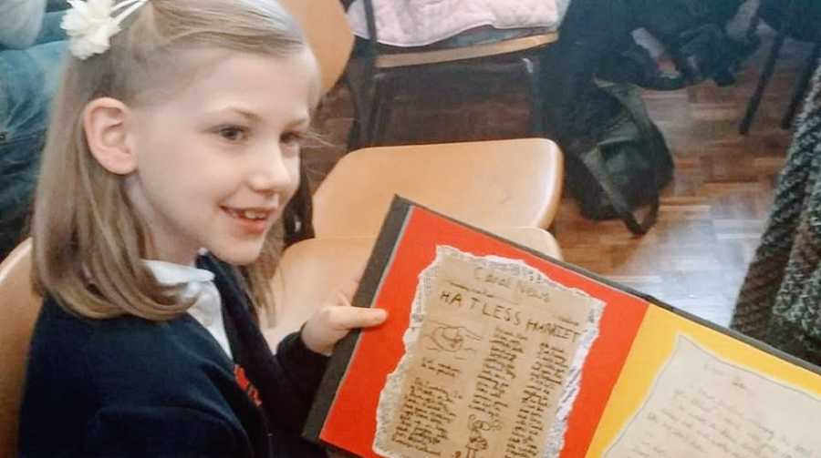 A girl with autism holds up a school project at her desk