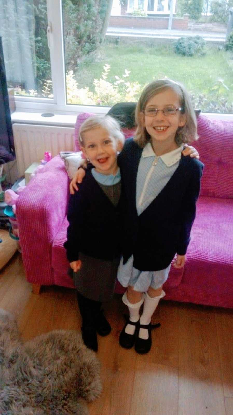 A pair of siblings stand together wearing school uniforms