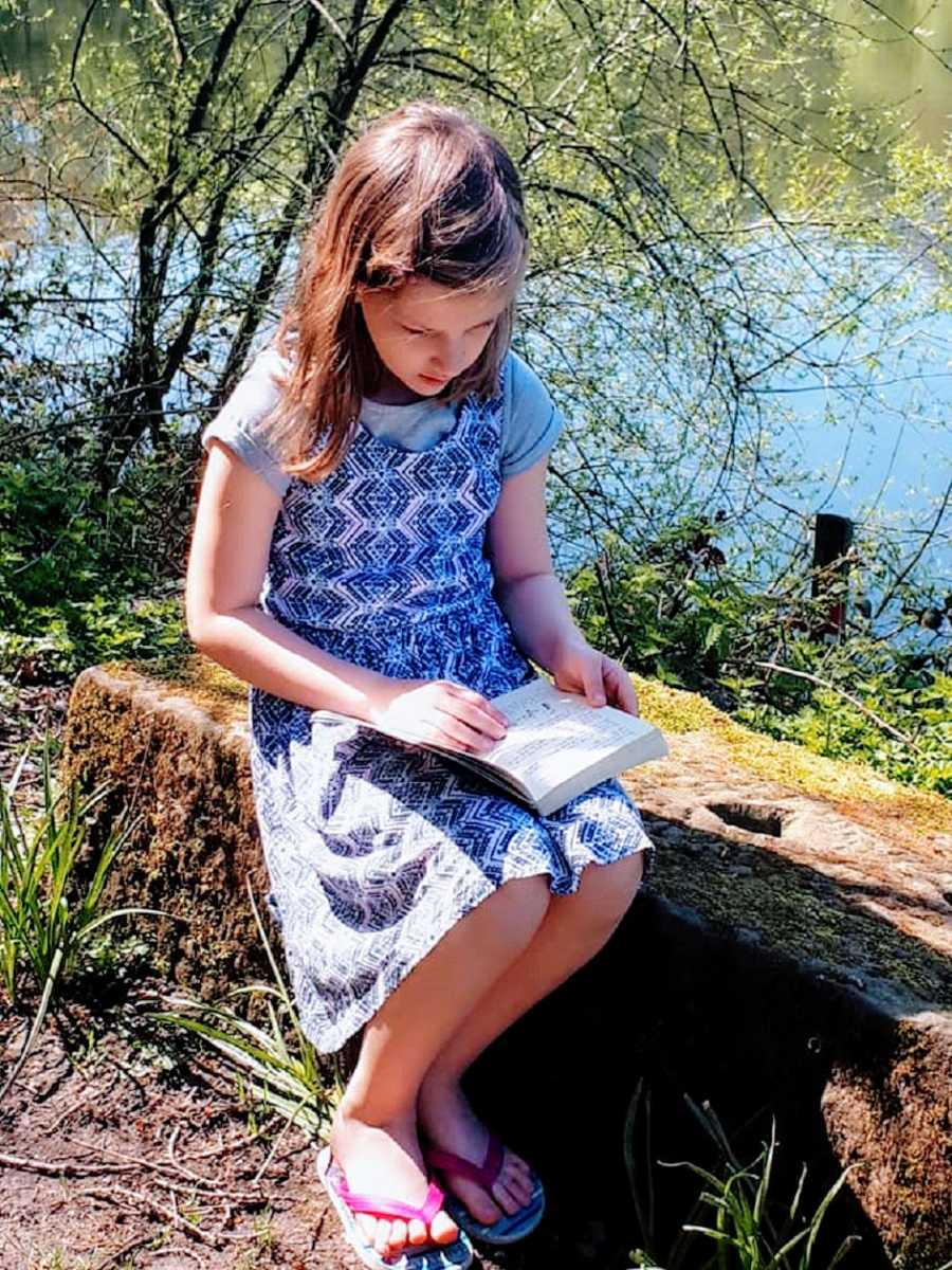 A girl in a blue dress reads a book outside