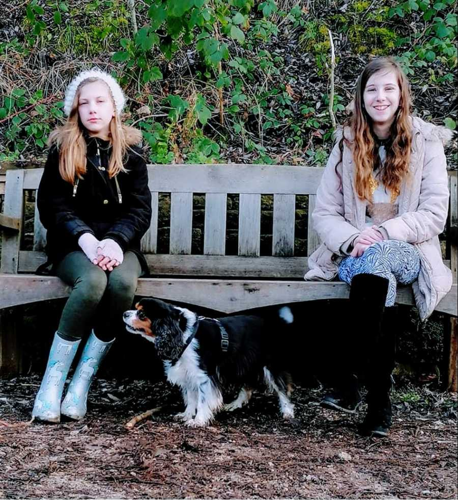 A pair of siblings sit on a park bench with a small dog between them