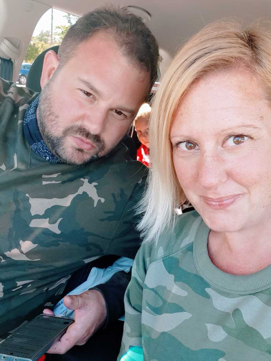 A woman and her husband wearing camouflage sit in their car