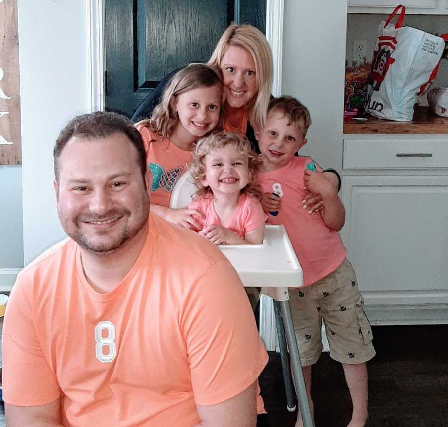 A woman with her three children and her husband, all dressed in orange