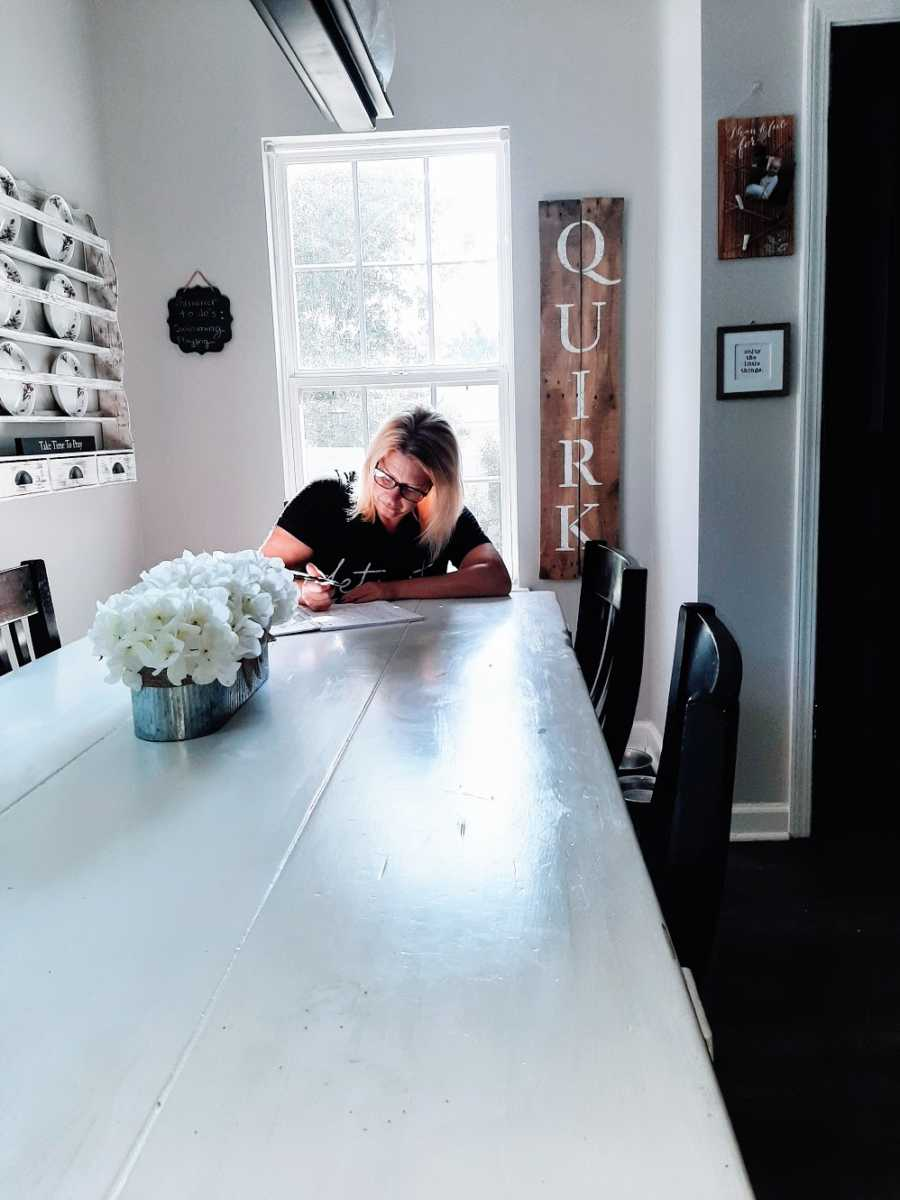 A woman sits at a long table writing