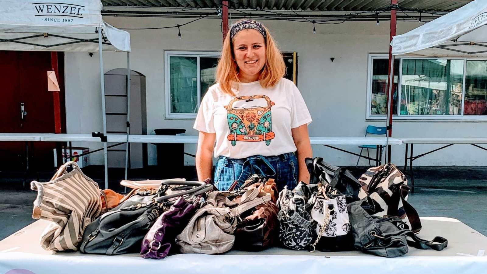 A young woman stands at a table covered in purses