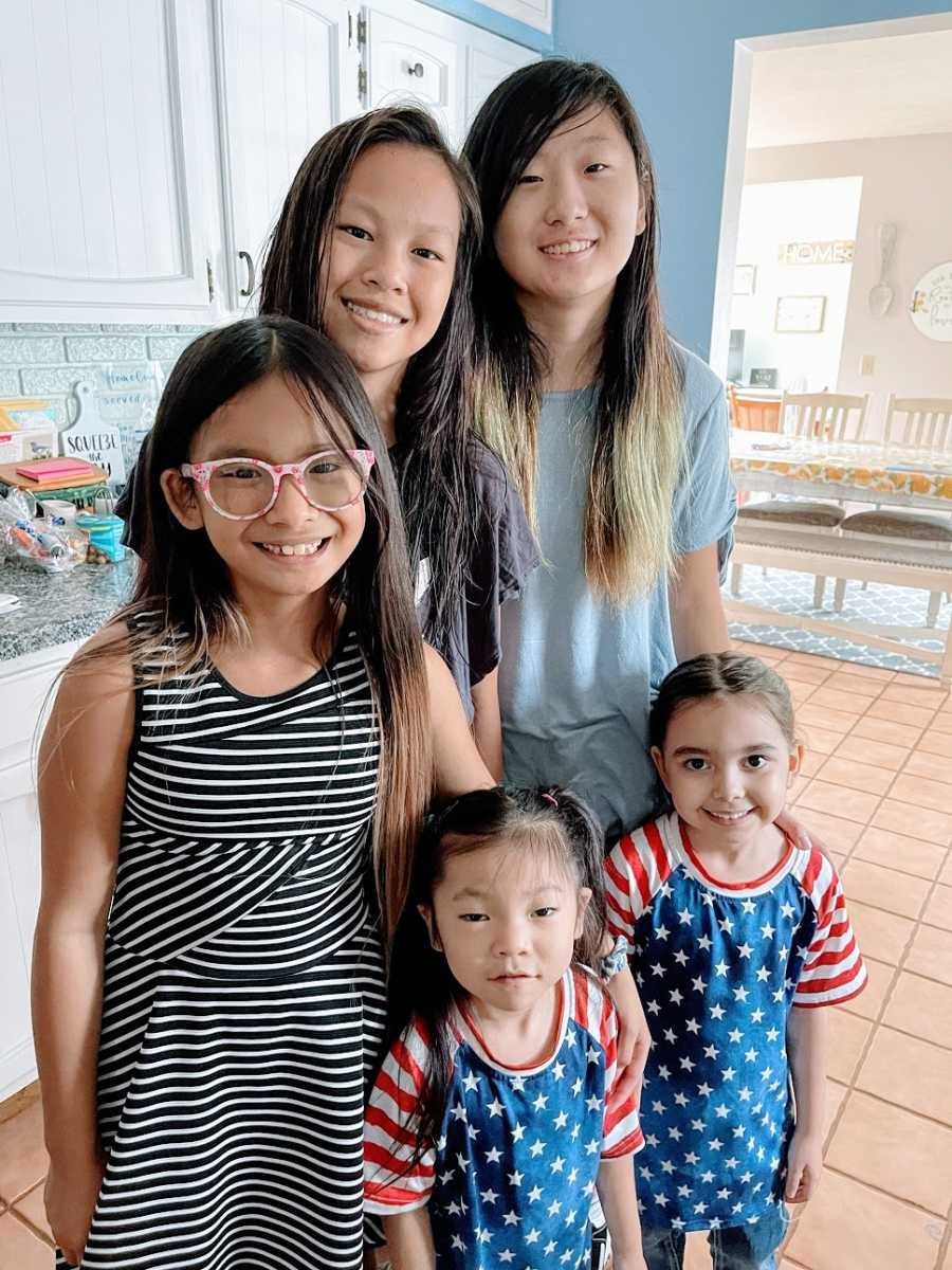 Five children stand together in a kitchen
