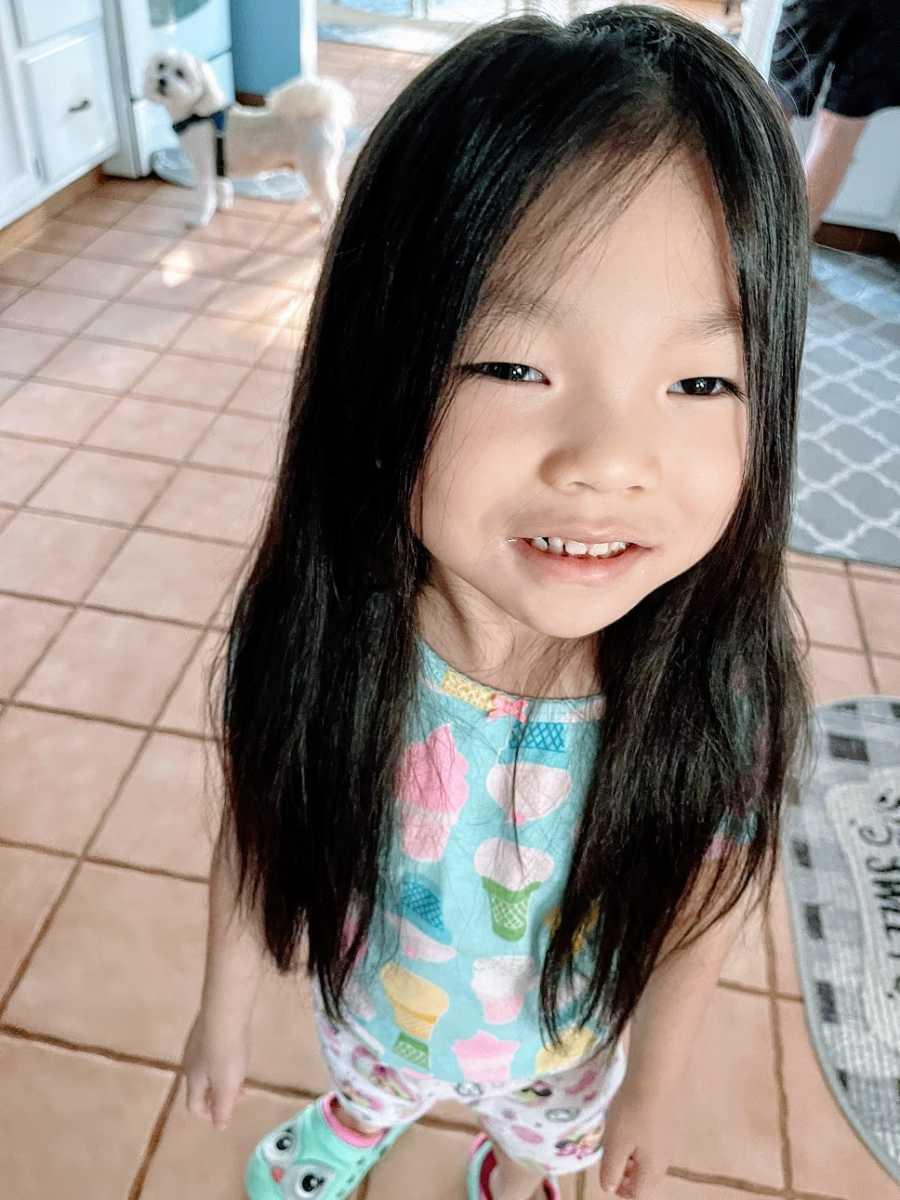 A little girl wearing a blue shirt and shorts