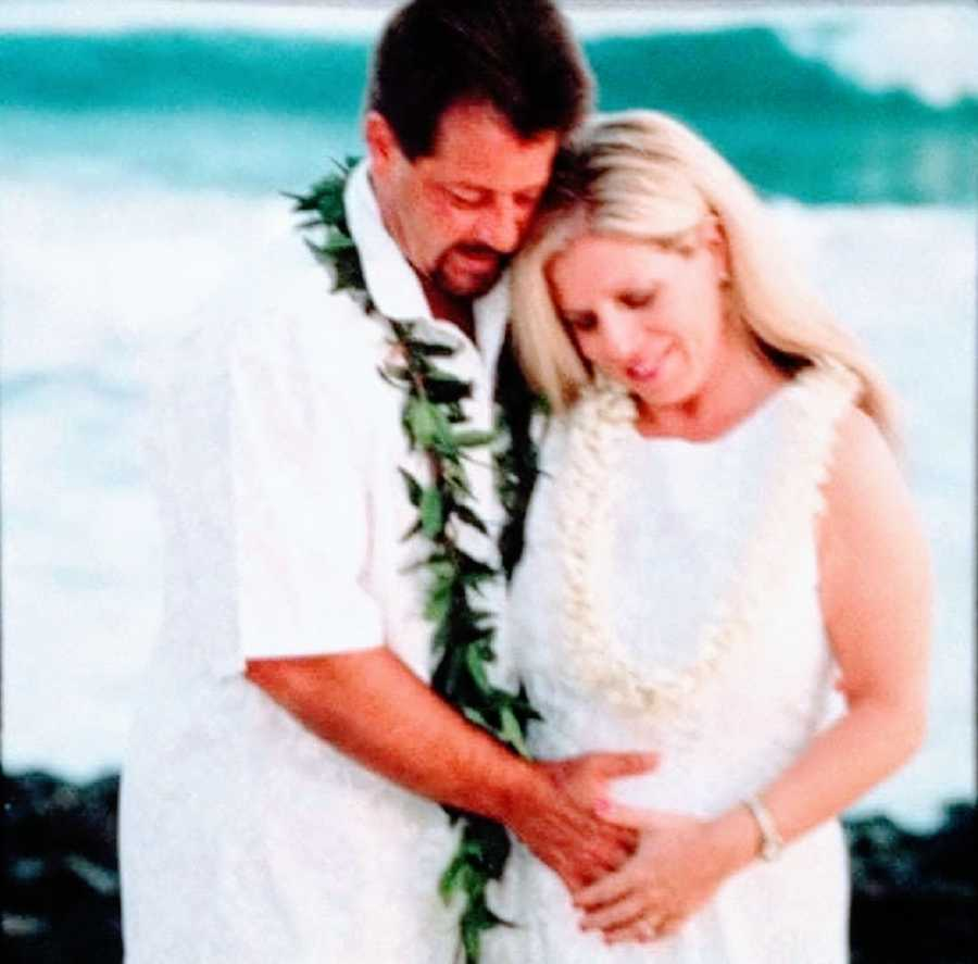 A husband and wife wearing leis and white shirts