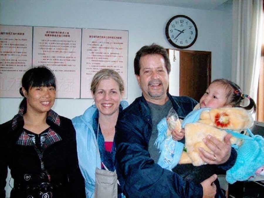 Parents stand holding their adopted baby girl
