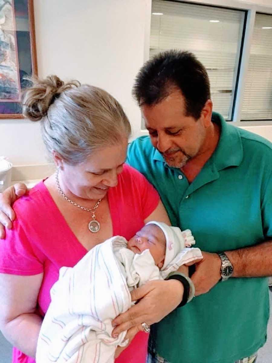 Parents hold their newborn baby girl