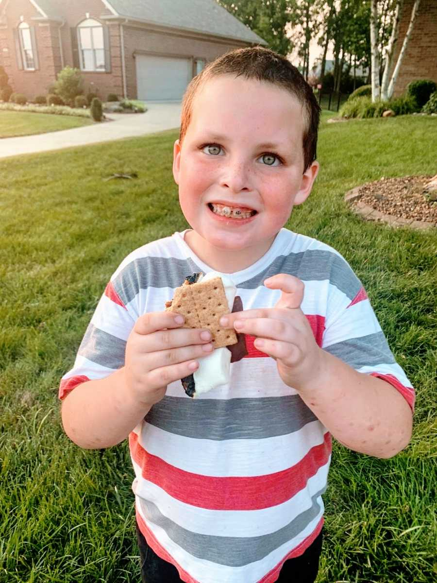 A boy with braces smiles while holding a s'more