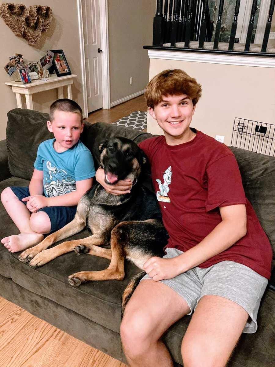 Brothers sit with a dog on the couch