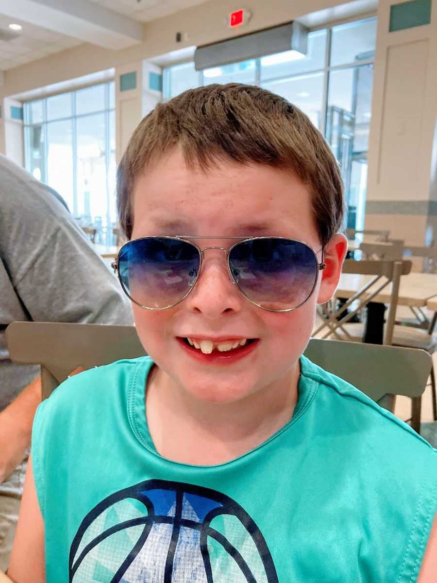 A boy wearing sunglasses sits in a grey chair