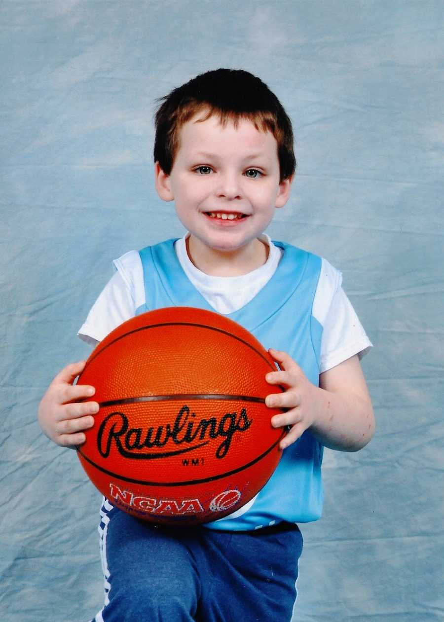 A little boy sits holding a basketball on his lap