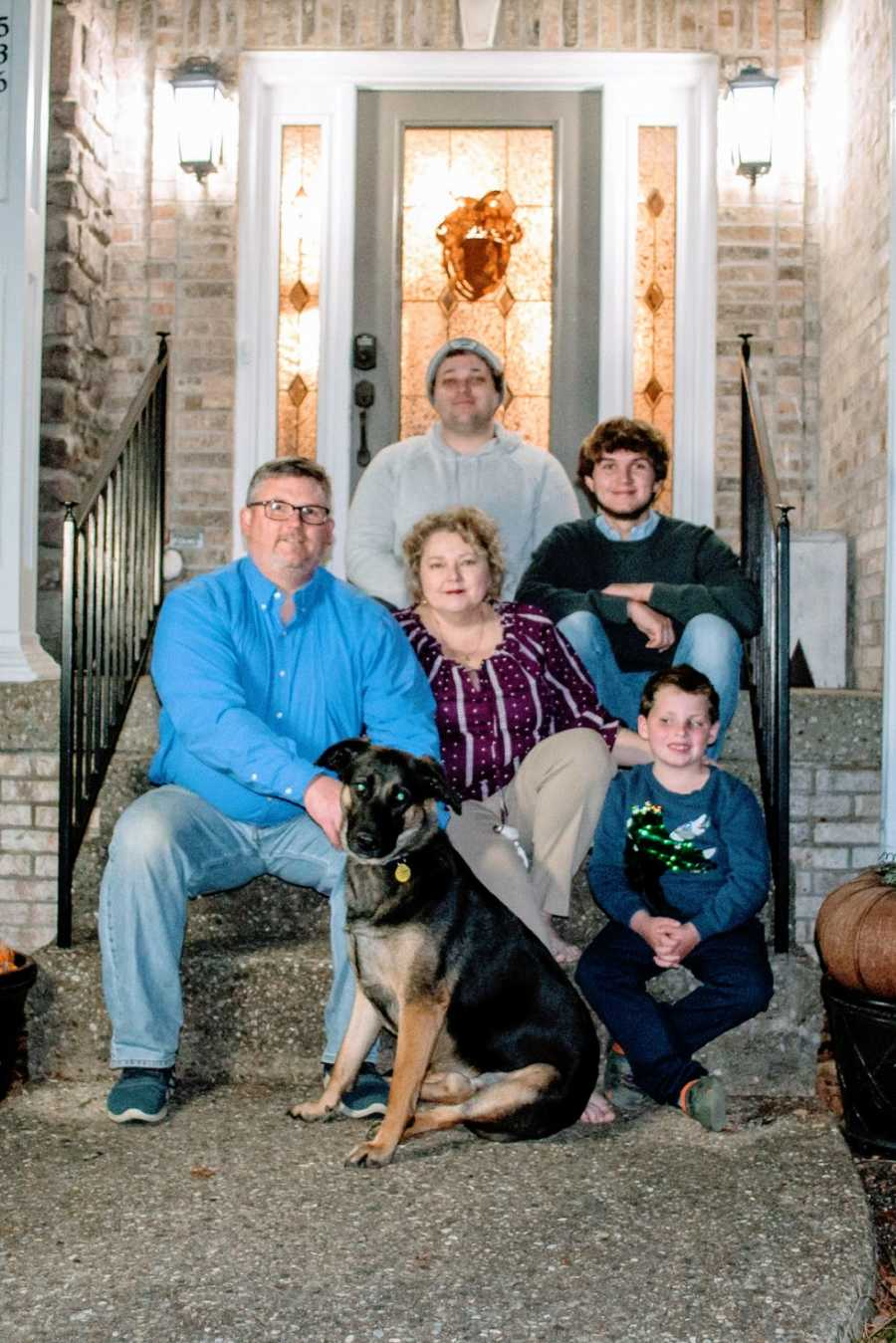 A family of five sit with their dog on their front steps