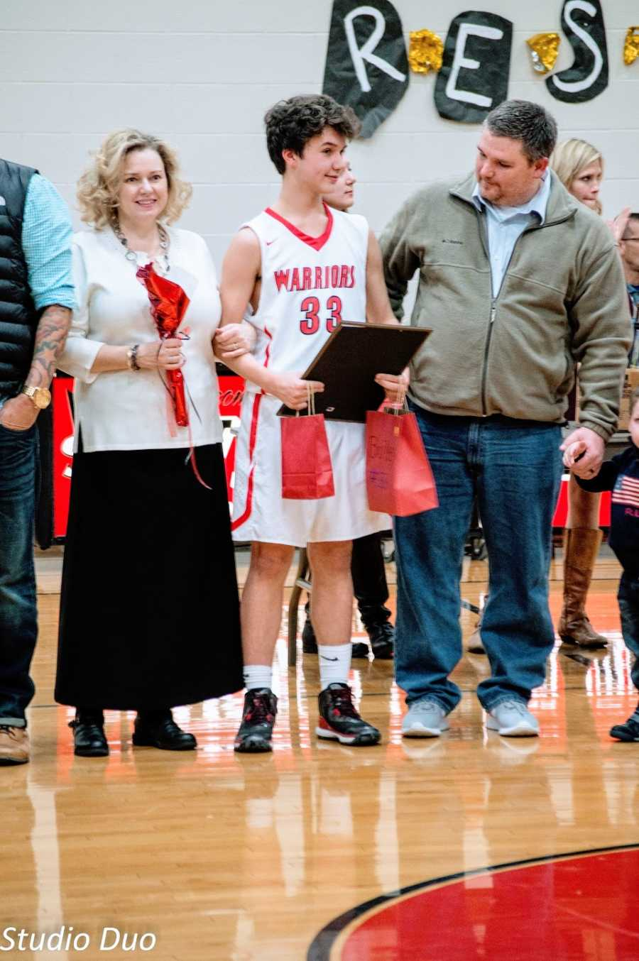 Parents stand in a gym with their son who wears a basketball uniform