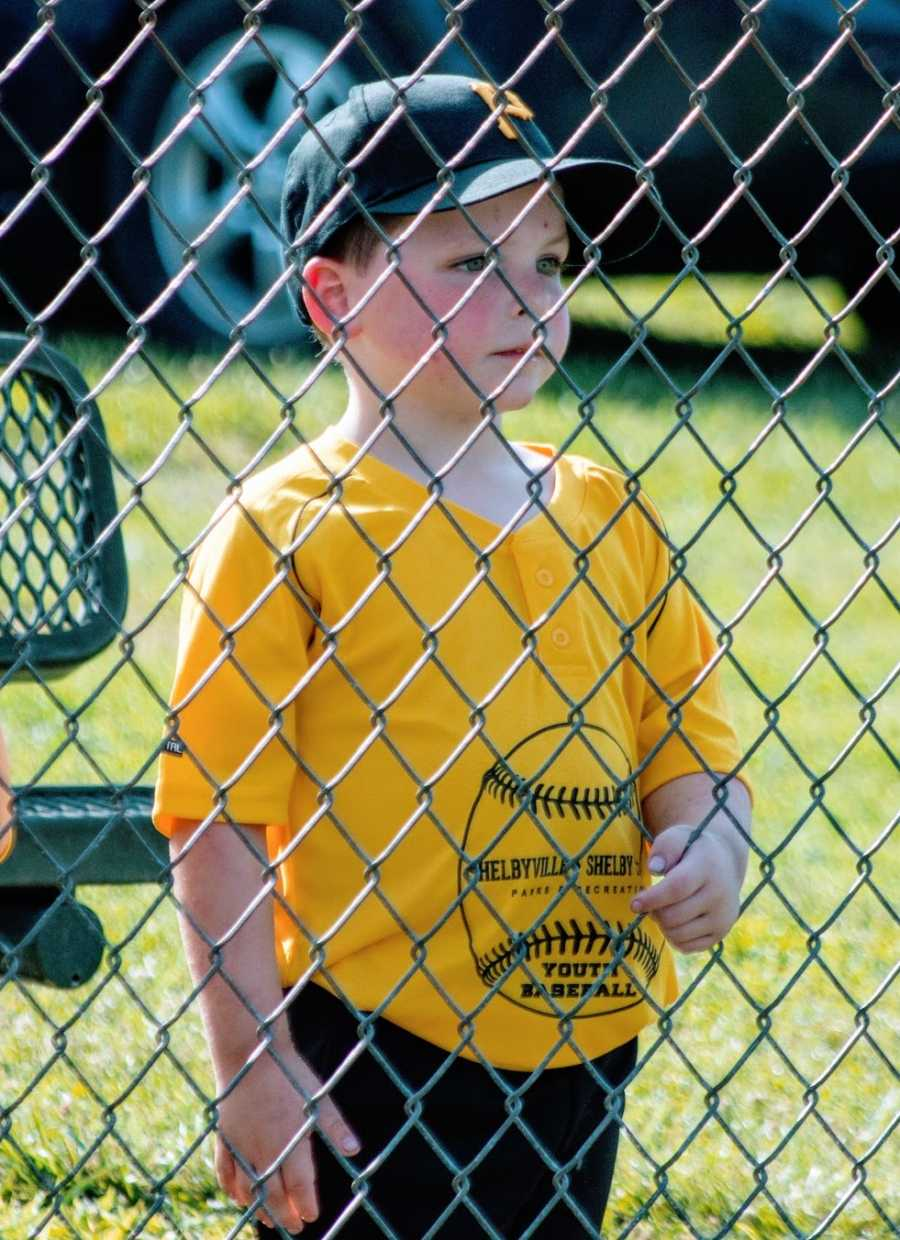 A boy wearing a baseball cap and yellow shirt stand behind a fence