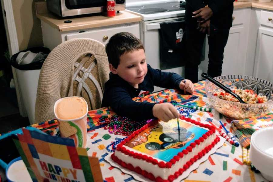 A little boy cuts into a cake on his birthday