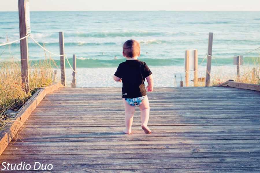 A toddler runs down a dock towards the water