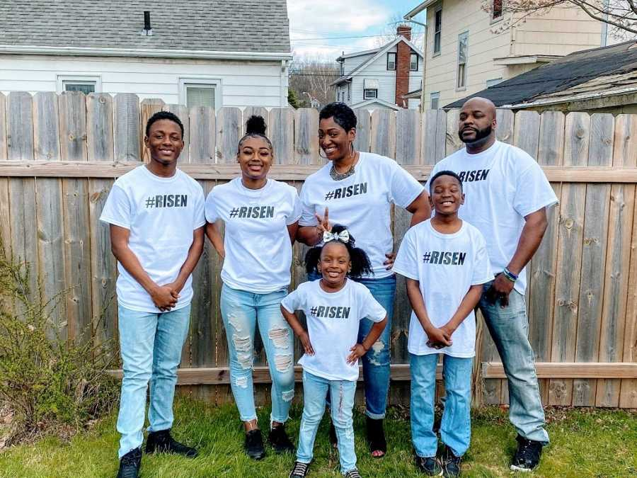 A family of 6 stand together wearing matching shirts