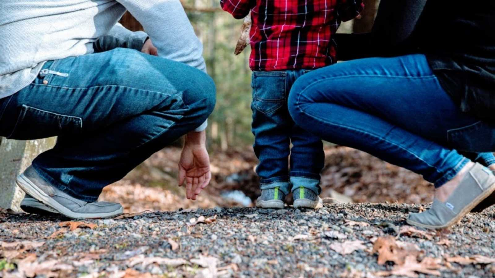 Parents kneel on the ground near a boy in a red plaid shirt